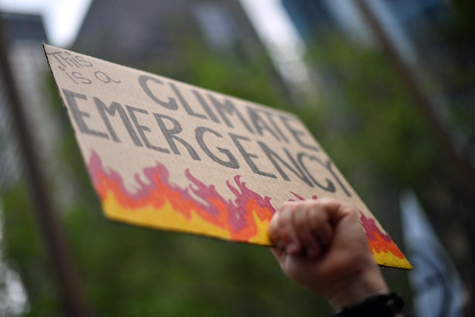 An attendee holds up a placard at a climate protest rally in Sydney on December 11, 2019. - Up to 20,000 protesters rallied in Sydney on December 11 demanding urgent climate action from Australia's government, as bushfire smoke choking the city caused health problems to spike. (Photo by Saeed KHAN / AFP) (Photo by SAEED KHAN/AFP via Getty Images)