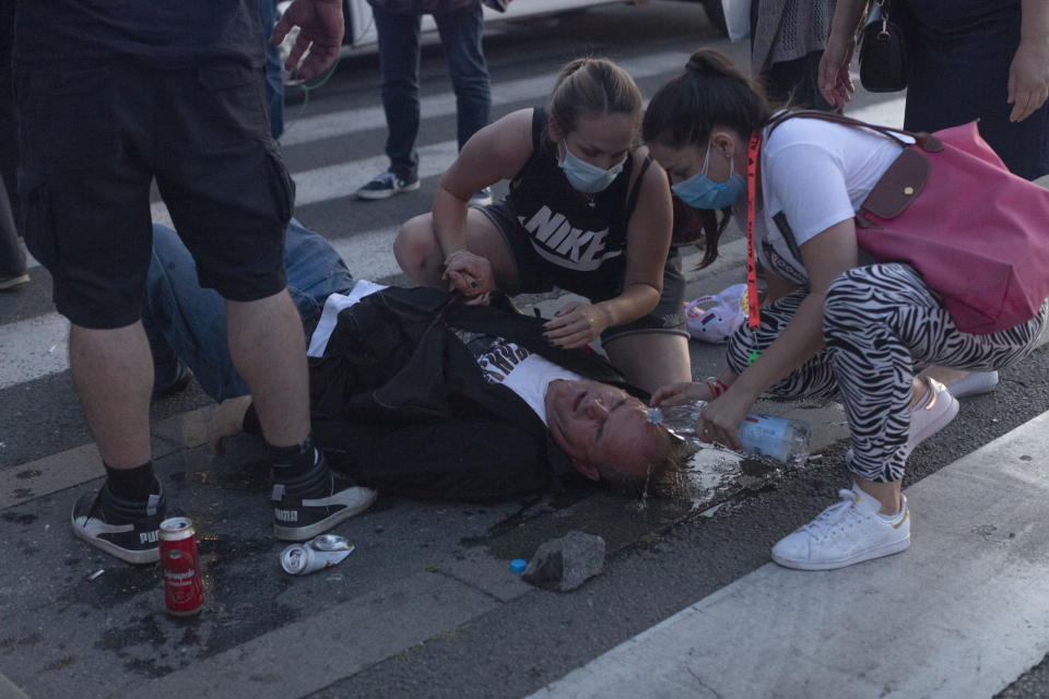 People tend to an injured man during a protest in Belgrade, Serbia, Wednesday, July 8, 2020. Police have fired tear gas at protesters in Serbia's capital during the second day of demonstrations against the president's handling of the country's coronavirus outbreak. President Aleksandar Vucic backtracked on his plans to reinstate a coronavirus lockdown in Belgrade this week, but it didn't stop people from firing flares and throwing stones while trying to storm the downtown parliament building. (AP Photo/Marko Drobnjakovic)