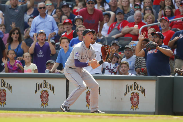 Colorado Rockies first baseman Ryan McMahon, center, reacts after dropping a foul ball pop-up in the ninth inning of a baseball game against the Atlanta Braves, Sunday, Aug. 19, 2018, in Atlanta. (AP Photo/Todd Kirkland)