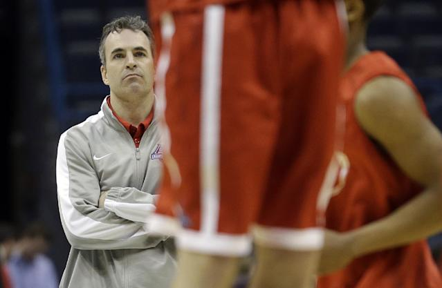 American University head coach Mike Brennan watches as his players warm up during a practice session for their NCAA college basketball tournament game Wednesday, March 19, 2014, in Milwaukee. American plays Wisconsin in round two on Thursday. (AP Photo/Morry Gash)