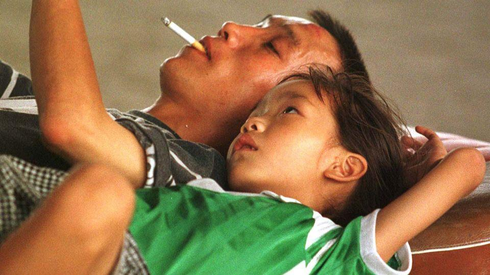 A Chinese man smoking a cigarette while reading to his daughter, under an overpass in Beijing. Source: AP
