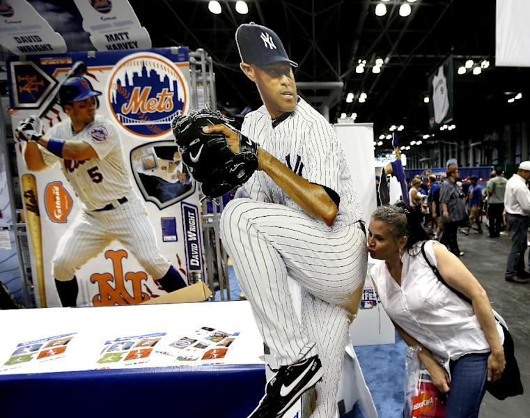 Evelis Cruz, of the Bronx borough of New York, kisses a cutout photo of New York Yankees pitcher Mariano Rivera while posing for a friend during the All-Star FanFest in New York's Javits Convention Center, Saturday, July 13, 2013. The five-day event is being held in conjunction with baseball's All-Star Game. (AP Photo/Julio Cortez)