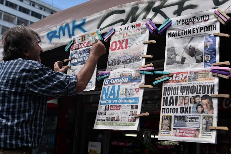 """A man hangs newspapers bearing """"No"""" and """"Yes"""" headlines in central Athens, on July 4, 2015, on the eve of the Greek referendum on its bailout terms (AFP Photo/Louisa Gouliamaki)"""