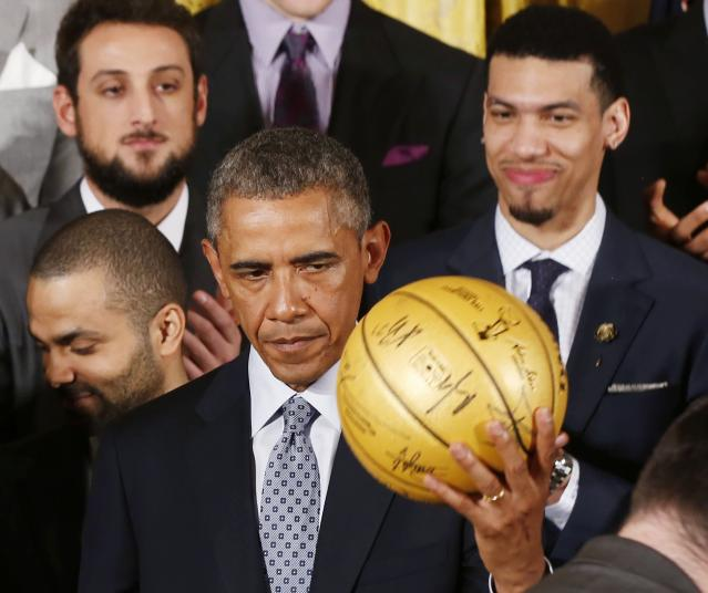 U.S. President Barack Obama holds up an autographed basketball as he welcomes the 2014 NBA Champion San Antonio Spurs to the East Room of the White House in Washington, January 12, 2015. REUTERS/Larry Downing (UNITED STATES - Tags: POLITICS SPORT BASKETBALL)