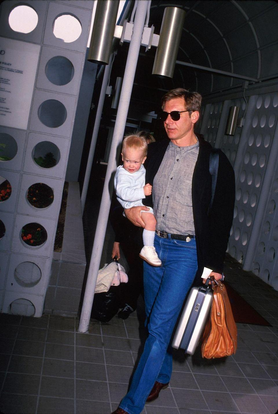 <p>In 1988, Harrison Ford makes his way through the airport with one very important carry-on: his son, Malcolm. </p>