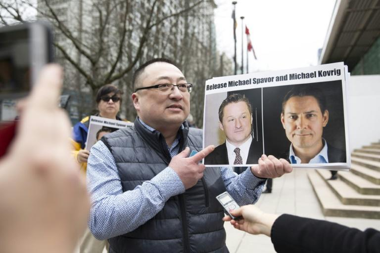 Louis Huang of Vancouver Freedom and Democracy for China holds photos of Canadians Michael Spavor and Michael Kovrig, who have been detained in China, outside the British Columbia Supreme Court in Vancouver on March 6, 2019