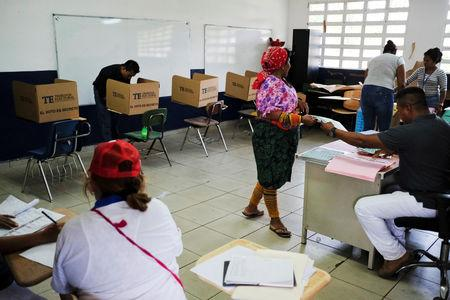 An indigenous woman receives a ballot paper at a polling station during the general election in Loma Cova, Panama May 5, 2019. REUTERS/Jose Cabezas