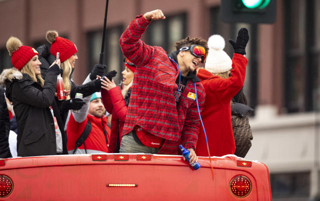 Chiefs QB Patrick Mahomes celebrates atop one of the team buses during the Super Bowl celebration parade. (Photo by David Eulitt/Getty Images)