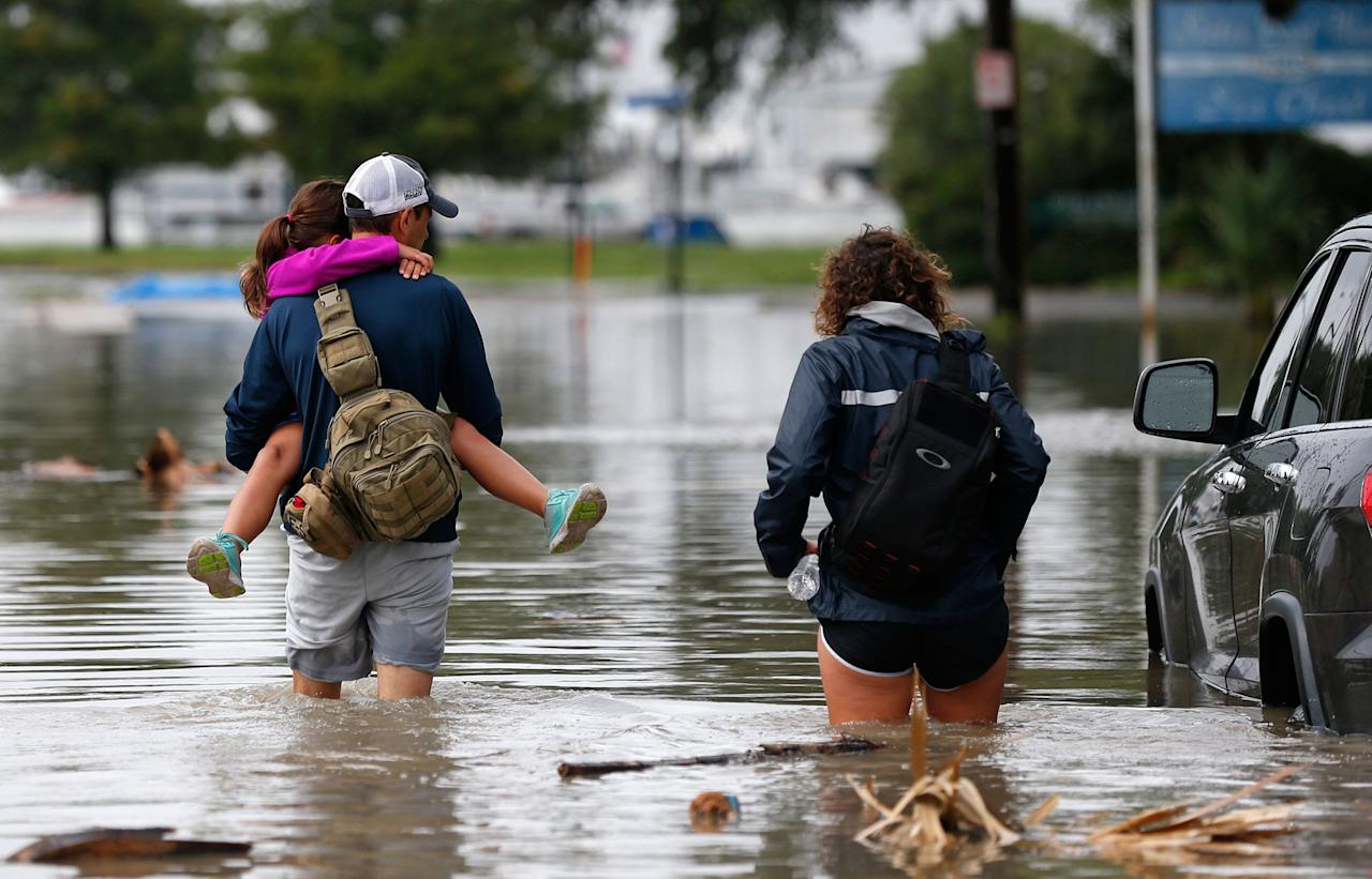 <p>Don Noel carries his daughter Alexis, 8, with his wife Lauren, right as they walk through a flooded roadway to check on their boat in the West End section of New Orleans, Wednesday, June 21, 2017. Tropical Storm Cindy formed Tuesday in the Gulf of Mexico, hovering south of Louisiana as it churned tides and spun bands of heavy, potentially flooding rain onto the central and eastern Gulf Coast. (Photo: Gerald Herbert/AP) </p>