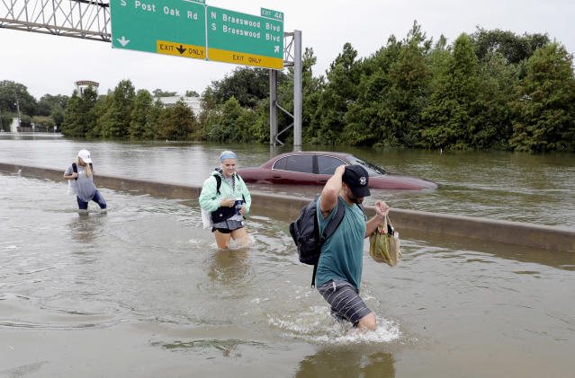 Evacuees wade down a flooded section of Interstate 610 as floodwaters from Tropical Storm Harvey rise Sunday, Aug. 27, 2017, in Houston, Texas. (AP Photo/David J. Phillip)