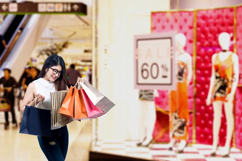 Happy beautiful asian young woman check goods in her shopping bags at shopping malls