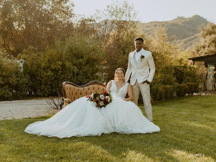 A bride sits on a couch outside and a groom sits next to her.