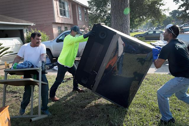 <p>Volunteers from Performance Contractors help co-worker Cornell Beasley recover from damage to his home after torrential rains caused widespread flooding during Hurricane and Tropical Storm Harvey on September 1, 2017 in Houston, Texas. Harvey, which made landfall north of Corpus Christi on August 25, dumped around 50 inches of rain in and around areas of Houston and Southeast Texas. (Photo: Scott Olson/Getty Images) </p>