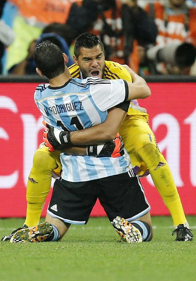 Argentina's Maxi Rodriguez, front, celebrates with goalkeeper Sergio Romero after scoring the decisive goal during the World Cup semifinal soccer match between the Netherlands and Argentina at the Itaquerao Stadium in Sao Paulo, Brazil, Wednesday, July 9, 2014. Argentina beat the Netherlands 4-2 in a penalty shootout to reach the World Cup final. (AP Photo/Frank Augstein)