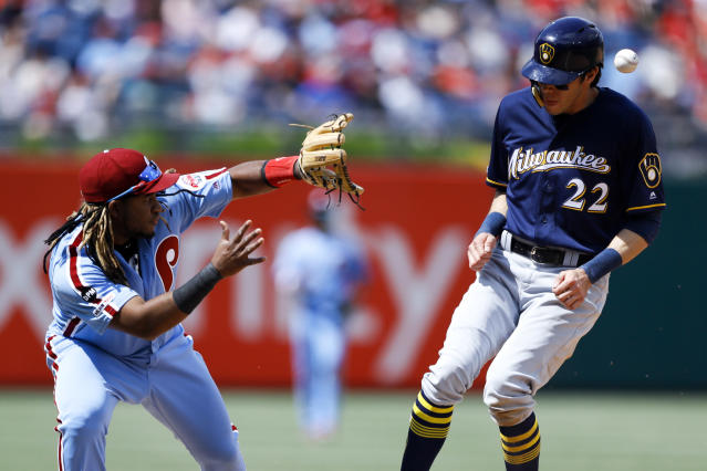 Milwaukee Brewers' Christian Yelich, right, is hit by a throw near Philadelphia Phillies third baseman Maikel Franco after Yelich advanced to third on an overthrow after stealing second during the sixth inning of a baseball game, Thursday, May 16, 2019, in Philadelphia. (AP Photo/Matt Slocum)