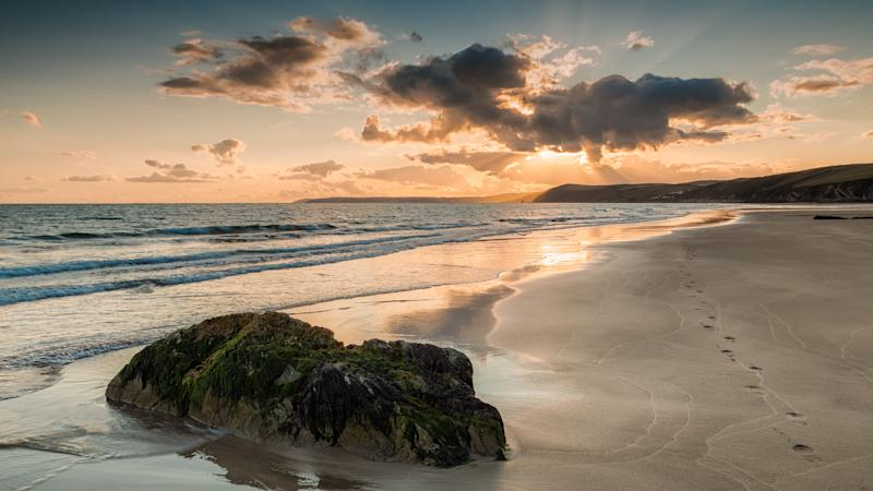 Tregantle Beach, Whitsand Bay, Cornwall. August 19, 2014. Footprints in the sand leading off to the sea, Fluffy clouds during a beautiful sunset at Whitsand Bay.