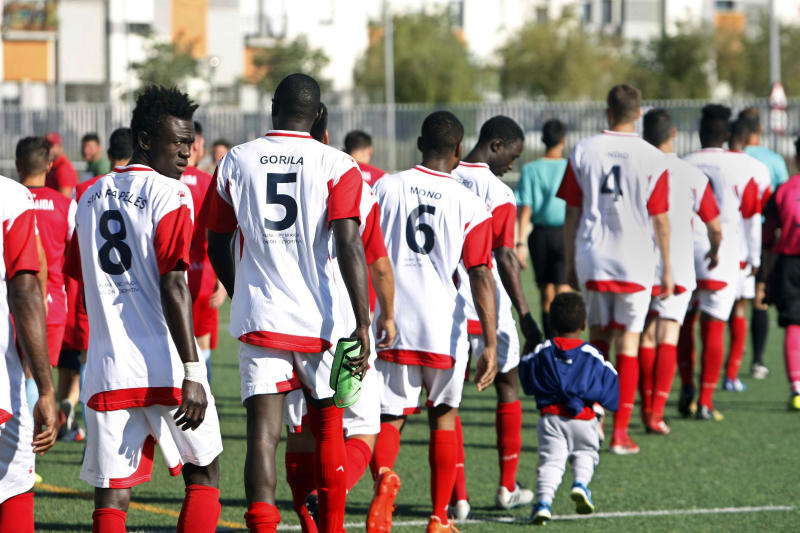 In this hand out photo taken on Sunday May 26, 2019, Spanish soccer team Alma de Africa, whose squad is composed of recently arrived migrants and Spaniards, walk in shirts that include insults they've had directed at them, in Jerez de la Frontera, Spain. A Spanish soccer team heavily composed of migrants has found a novel way to protest against the racist abuse the players have received. The players of Alma de Africa - Spanish for 'Soul of Africa' - have decided to don shirts that have the insults hurled at them printed on their back instead of their names. (Vanesa Lobo/Diario de Jerez via AP)
