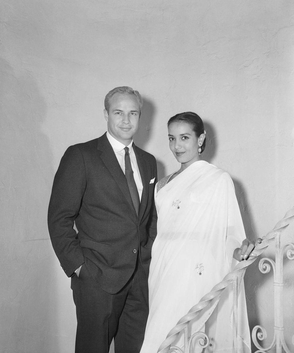 """<p>Marlon Brando's first wife was British Indian actress Anna Kashfi. The two eloped in 1957 and said """"I do"""" in Eagle Rock, California. They separated shortly after welcoming their son, Christian Devi Brando, in 1958—which spurred a <a href=""""https://www.latimes.com/local/obituaries/la-me-anna-kashfi-20150825-story.html"""" rel=""""nofollow noopener"""" target=""""_blank"""" data-ylk=""""slk:bitter custody battle"""" class=""""link rapid-noclick-resp"""">bitter custody battle</a> between the exes.</p>"""