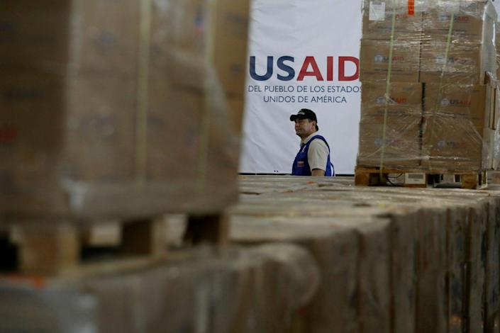 A man walks past boxes of stockpiled USAID humanitarian aid meant for Venezuela at a warehouse in Colombia.