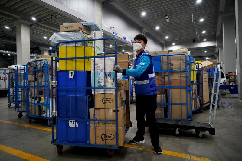 FILE PHOTO: A delivery man for Coupang Jung Im-hong wearing a mask to prevent contracting the coronavirus, loads packages before leaving to deliver them in Incheon