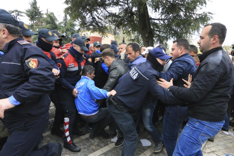 Protesters clash with police front of the Albanian parliament building in Tirana, on Thursday, March 28, 2019. Albanian opposition protesters have repeated attempts to enter the parliament by force in their protest asking for the government's resignation and an early election.(AP Photo/ Hektor Pustina)