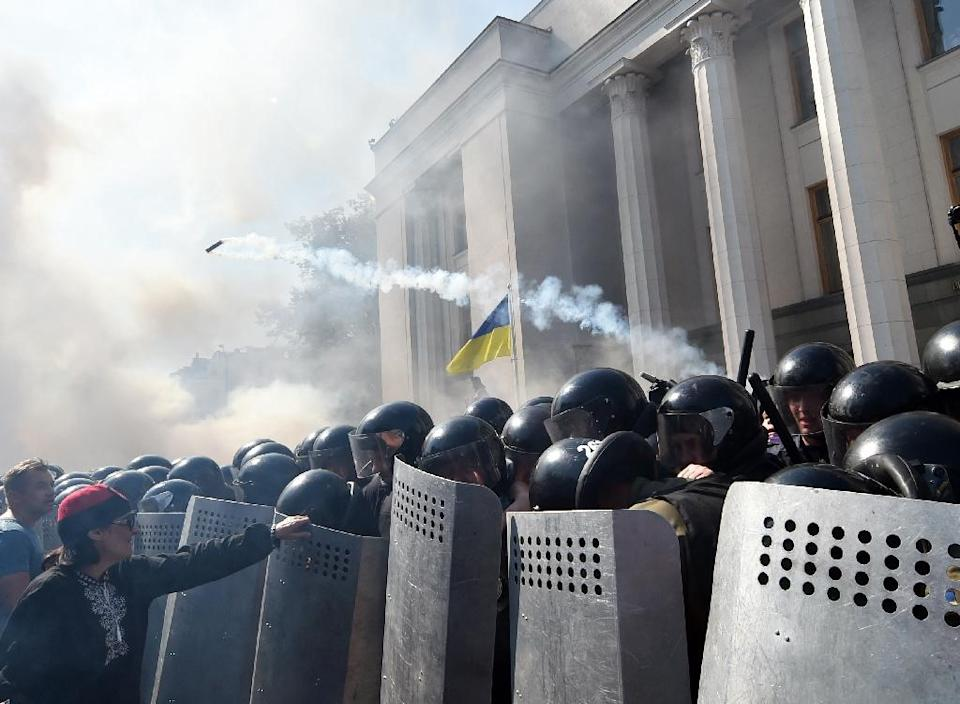 A demonstrator holds a police officer's shield in front of the parliament building in Kiev during clashes with police officers on August 31, 2015 (AFP Photo/Sergei Supinsky)