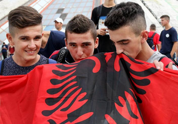 Football fans kiss the Albanian flag as they protest on October 16, 2014 near the Serbian Embassy in Tirana (AFP Photo/Gent Shkullaku)
