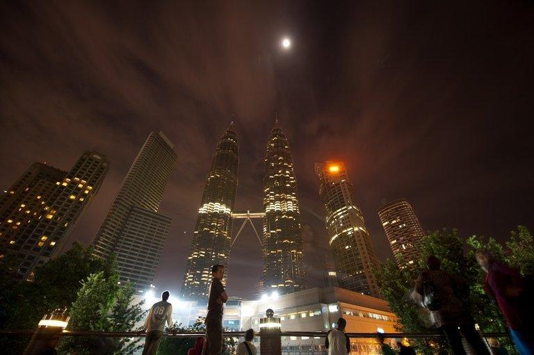 People gather in front of Malaysia's iconic Patronas Twin Towers in Kuala Lumpur on March 31, 2012