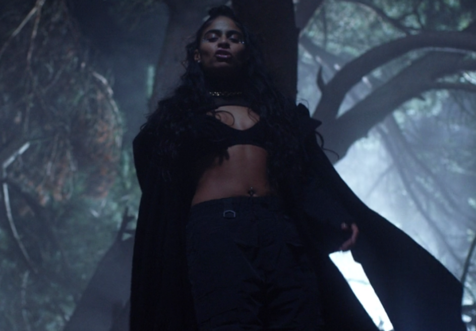 """<p>Flanked by two dancers, Reyez performs """"Scar"""" during a dramatic scene in the woods.</p>"""