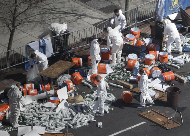 Investigators comb through the post finish line area of the Boston Marathon at Boylston Street, two days after two bombs exploded just before the finish line, Wednesday, April 17, 2013, in Boston. (AP Photo/Julio Cortez)