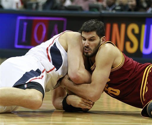 Cleveland Cavaliers forward Omri Casspi (36), right, and Atlanta Hawks center Zaza Pachulia (27) wrestle for a loose ball in the first half of an NBA basketball game on Saturday, Jan. 21, 2012, in Atlanta. (AP Photo/John Bazemore)