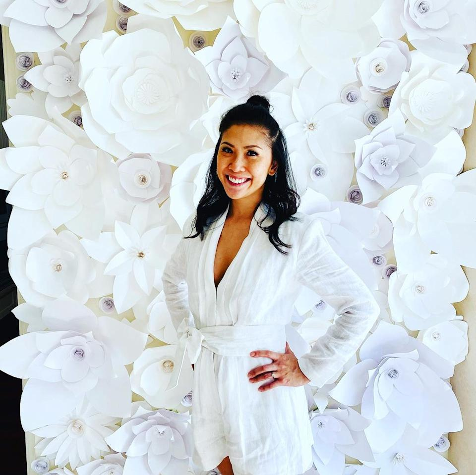 wedding paper flower wall with bride standing in front