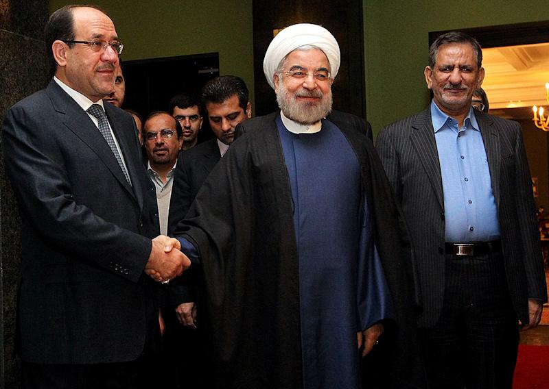 Iranian President Hassan Rouhani (centre) greets Nuri al-Maliki (left) in Tehran on December 5, 2013 (AFP Photo/)