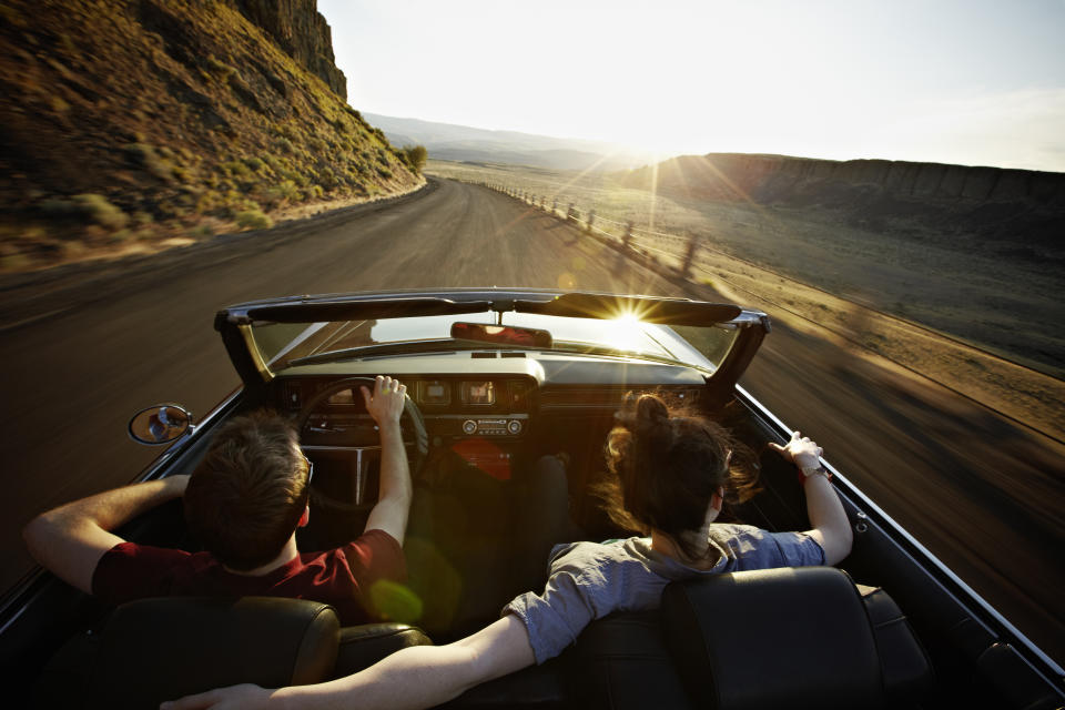 Young couple driving convertible at sunset on desert road