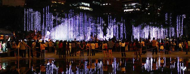 Five days before Christmas locals watch the lights and sound show called Spectacular Spectrum at the Ayala Triangle Gardens in Makati City. It features inflatable stars and gobo lights with LED string lights and laser lights and fog machines. The show that fascinates passersby of the Ayala Triangle Garden began last November 16 and will end on December 30. (Marlo Cueto/NPPA Images)