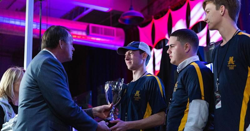 """Students from Georgia's Mt. De Sales Academy esports team receive a trophy after competing in the state's PlayVS """"League of Legends"""" championship in May 2019."""