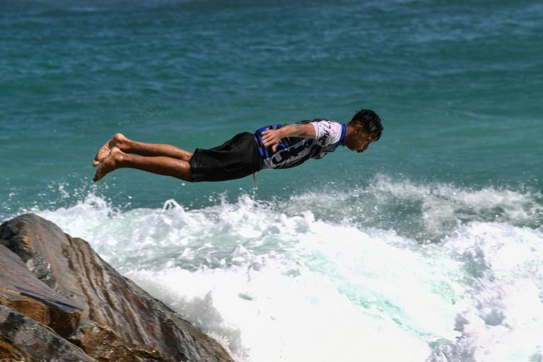 A youngster dives into the sea at Camurichico beach in La Guaira