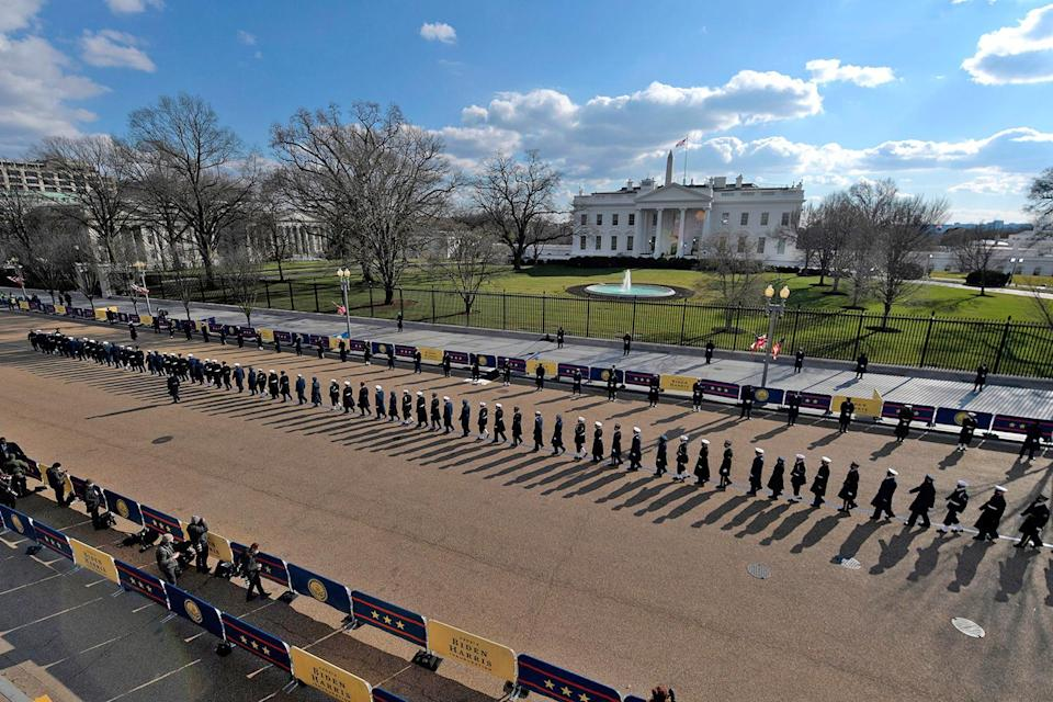 <p>An honor guard lines up outside the White House, surrounded by Biden-Harris banners. </p>