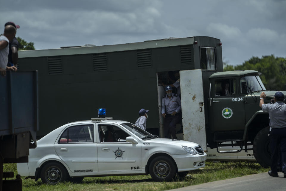 A police officer exits a police truck for transporting prisoners after detaining and placing demonstrators inside during a protest in Havana, Cuba, Sunday, July 11, 2021. Hundreds of demonstrators went out to the streets in several cities in Cuba to protest against ongoing food shortages and high prices of foodstuffs, amid the new coronavirus crisis. (AP Photo/Ramon Espinosa)