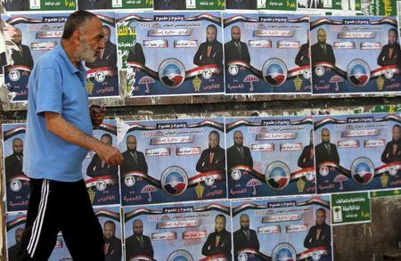 A man walks past election posters for parliamentary candidates of the Nour party Hossam Abdo and Mohammed Osama in the Imbaba district of Giza, Egypt, October 13, 2015.    REUTERS/Mohamed Abd El Ghany
