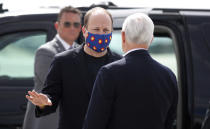 Gov. Jared Polis, center, wears a mask as he talks with Vice President Mike Pence as he arrives at Peterson Air Force Base Saturday, April 18, 2020, in Colorado Springs, Colo. Pence was on his way to speak at the graduation ceremony for the class of 2020 at the U.S. Air Force Academy. (AP Photo/David Zalubowski)