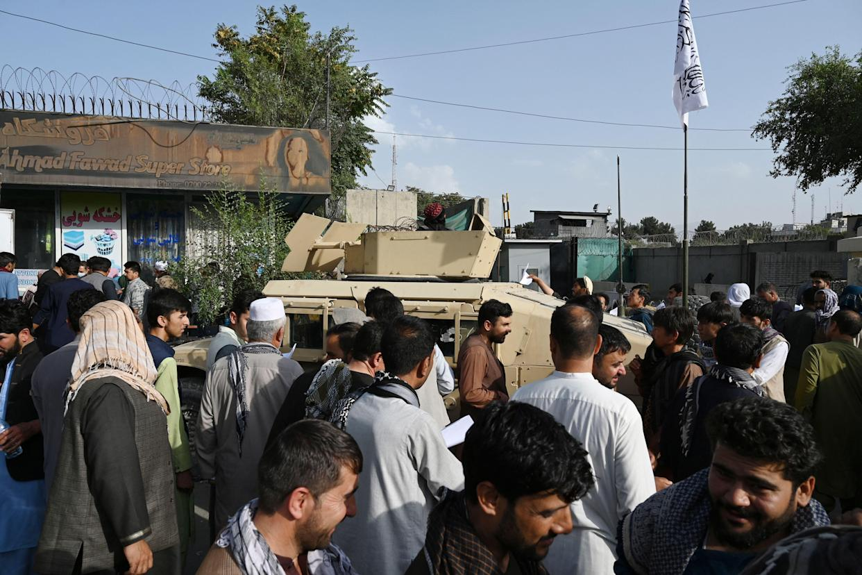 Afghan people wanting to leave the country queue up in front of the British and Canadian embassy in Kabul on August 19, 2021 after Taliban's military takeover of Afghanistan.   / AFP / WAKIL KOHSAR