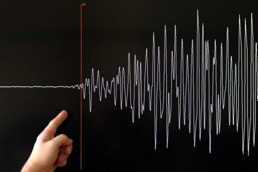 A scientist points to a seismograph of a major earthquake