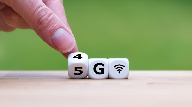 A man turns die so they read 5G instead of 4G, with a wireless coverage signal