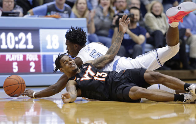North Carolina's Nassir Little (5) and Virginia Tech's Ahmed Hill (13) fall to the floor while chasing a loose ball during the first half of an NCAA college basketball game in Chapel Hill, N.C., Monday, Jan. 21, 2019. (AP Photo/Gerry Broome)
