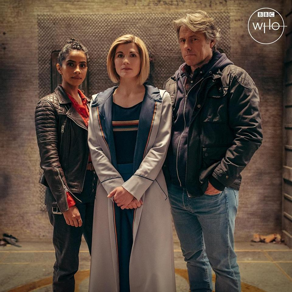 Yaz (Mandip Gill) wears a leather jacket, the Doctor (Jodie Whittaker) wears her usual costume, and Dan (John Bishop) wears a jacket and jeans, in a promo image for the new series of Doctor Who.