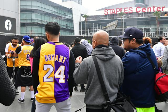 People gather around a makeshift memorial for former NBA and Los Angeles Lakers player Kobe Bryant after learning of his death at LA Live plaza in front of Staples Center in Los Angeles on January 26, 2020. - NBA legend Kobe Bryant died January 26, 2020 in a helicopter crash in suburban Los Angeles, celebrity website TMZ reported, saying five people are confirmed dead in the incident. (Photo by Frederic J. Brown / AFP) (Photo by FREDERIC J. BROWN/AFP via Getty Images)