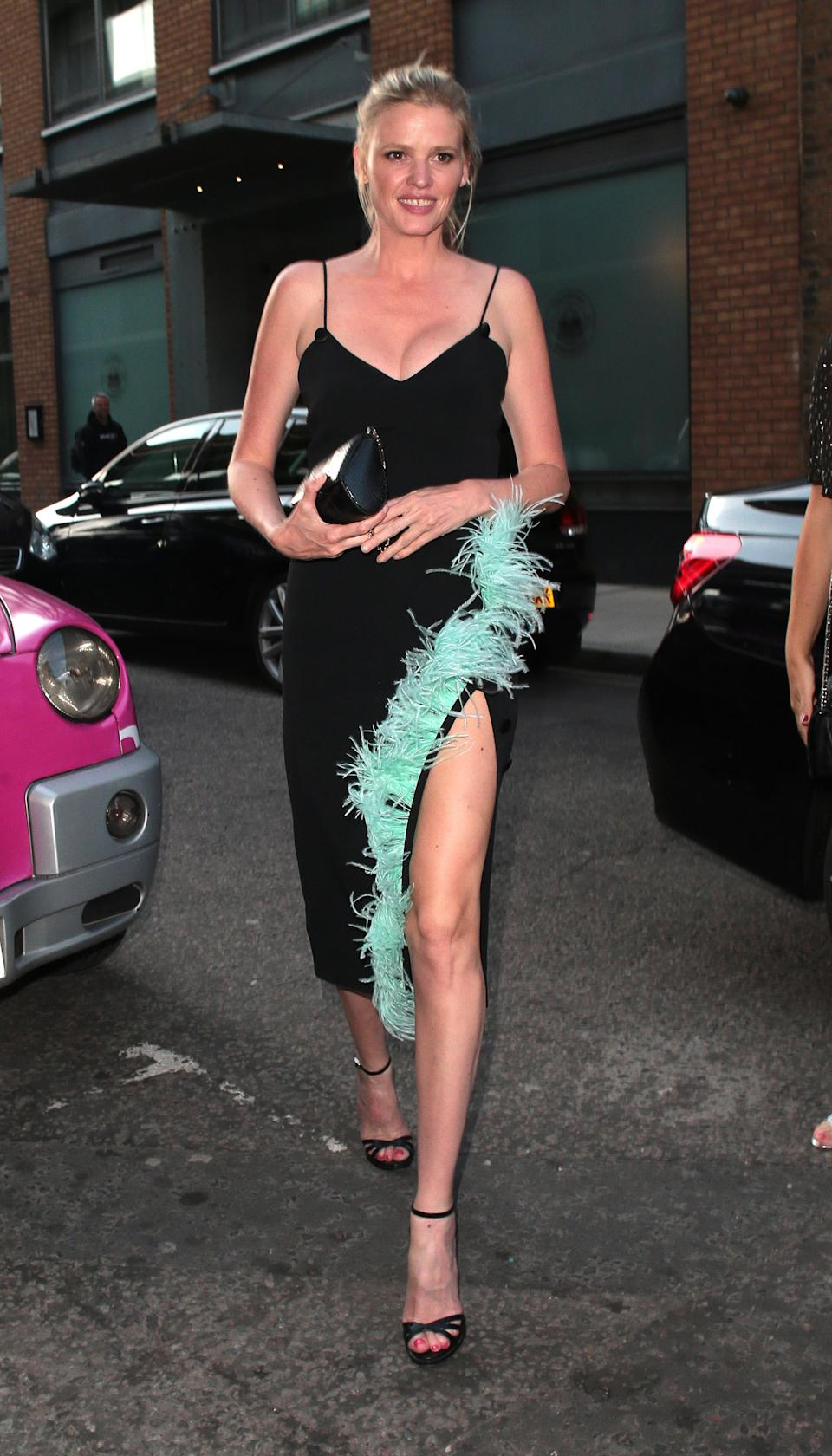 <p>Lara Stone shows off her impressive pins at the Nobu Hotel Shoreditch official launch in London, wearing a black, strappy dress lined with turquoise feathers. <em>[Photo: Getty]</em> </p>