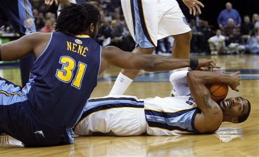 Memphis Grizzlies guard Mike Conley (11) calls for a timeout as Denver Nuggets forward Nene (31) wrestles him for the ball in the first half of an NBA basketball game Tuesday, Jan. 31, 2012, in Memphis, Tenn. (AP Photo/Alan Spearman)
