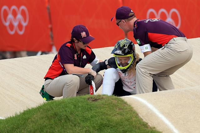 LONDON, ENGLAND - AUGUST 08: Brooke Crain of the United States is helped up after falling during the Women's BMX Cycling on Day 12 of the London 2012 Olympic Games at BMX Track on August 8, 2012 in London, England. (Photo by Phil Walter/Getty Images)